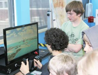 The new aeronautics classroom at the Aspen Middle School not only has an actual full-motion flight simulator, it also has four computer flight simulators for students to access. Canaan Case pilots a flight over Key West, Florida, as his co-pilot, Charlie Guilander, standing, gives flight tips. Both are eight-graders at the middle school.