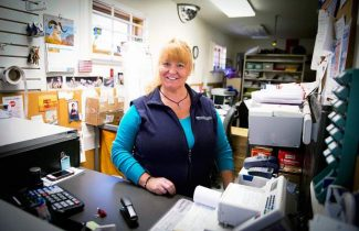 Woody Creek postmaster Sherry Mahoney will lose her full-time work status in January 2015 if current postal cutback plans stay as scheduled.