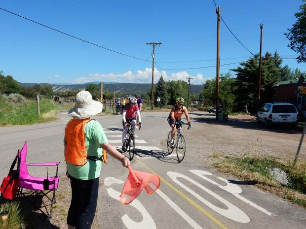 Cindy Smith, left, guides riders off Hooks Lane and onto the Rio Grande bike path on Sunday. The Ride the Rockies route used the Rio Grande for a short distance before putting riders on Upper and Lower River Roads.