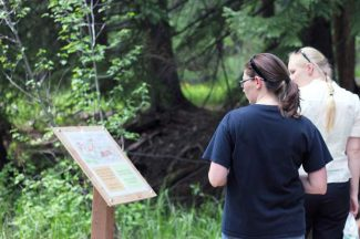 Pitkin County Library employees Kelly Benninger (dark shirt) and Anne Brookhart read one of the storyboards set up along the Hunter Creek extension trail as part of the StoryWalk Project.