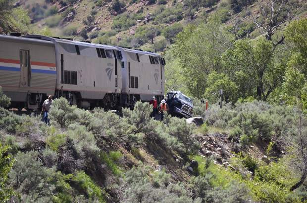 Workers examine the damage from Tuesday's train-truck crash.