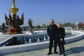 Johnny and Jan Walker stand in front of a fountain in North Korea, marking the 175th country Johnny Walker has visited.