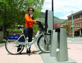 Mirte Mallory stands next to a WE-cycle station on the east side of the Rubey Park bus terminal in this Aspen Times file photo. Mallory is director of the bike-sharing system, which began in Aspen in 2013, is slated to expand to Basalt this summer and is being considered for Glenwood Springs.