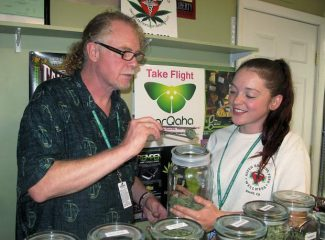 Aspen Roaring Fork Wellness employee Greg Gissler and shop manager Kerry Weber prepare some medical marijuana for a patient on Friday. The business also offers yoga classes and massages, but can't sell products for those services because of county marijuana regulations.