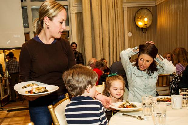 Amanda Rae volunteers her time at the Aspen TREE  free 9th annual community dinner at Hotel Jerome Tuesday evening to serve guests Amy Riley and her children Anna and Elliot.