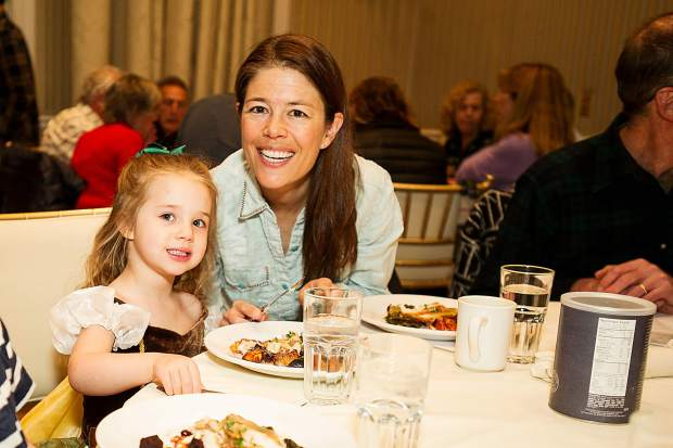 Amy Riley and her daughter Anna enjoy the 9th annual free community farm-to-table dinner at Hotel Jerome on Tuesday evening.