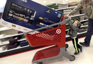 FILE - In this Friday, Nov. 25, 2016, file photo, Hunter Harvey, 2, helps his dad, C.J., wheel a big screen TV at Target, in Wilmington, Mass.   On Tuesday, Nov. 29, the Commerce Department reports the second of three estimates for the third quarter on the U.S. gross domestic product. (AP Photo/Elise Amendola, File)