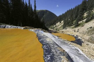 FILE - In this Aug. 14, 2015, file photo, water flows through a series of sediment retention ponds built to reduce heavy metal and chemical contaminants from the Gold King Mine wastewater accident in the spillway about 1/4 mile downstream from the mine outside Silverton, Colo. On Monday, Nov. 28, 2016, the U.S. Supreme Court asked the Justice Department to weigh in on New Mexico's lawsuit against Colorado over the Gold King mine waste spill that polluted rivers in both states and in Utah. (AP Photo/Brennan Linsley, File)