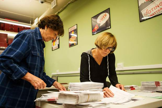 Frieda Wallison, left, and Ellen Marshall, aid in the ballot voter election process at the Pitkin County Clerk and Recorder's Office on Friday.