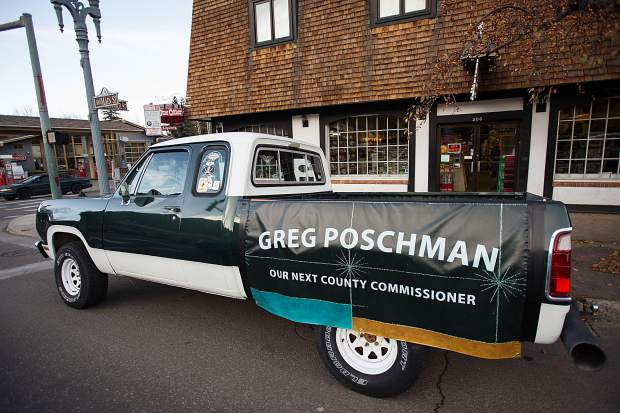 A truck with a banner supporting County Commissioner Greg Poschman sits outside of Carl's Pharmacy on Tuesday.