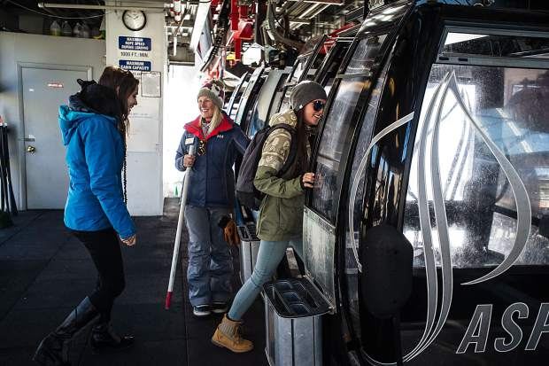 Taylor Russack escorts Emily Walsh, right, and Erica Stemple, along with her cat Paine onto the gondola at Aspen Mountain Friday afternoon.