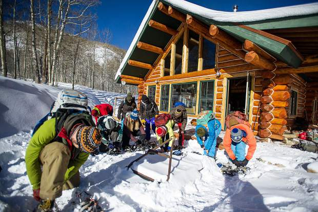 Future naturalists for the Aspen Center for Environmental Studies strap on snowshoes during training Wednesday morning at King's Cabin in Ashcroft before touring the routes they will lead guests on this winter.
