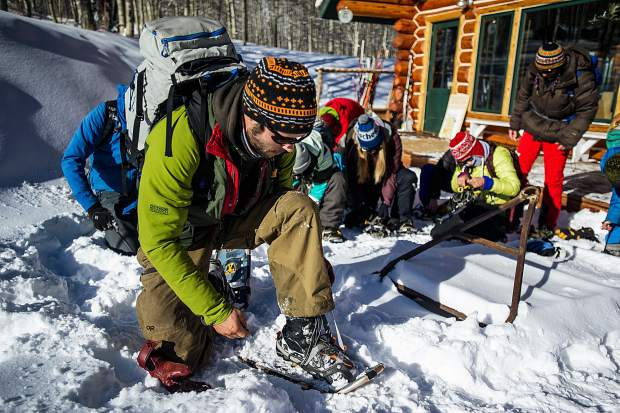 Sam Hinkle, a future naturalist for the Aspen Center for Environmental Studies straps on snowshoes during training Wednesday morning at King's Cabin in Ashcroft before touring the routes they will lead guests on this winter.