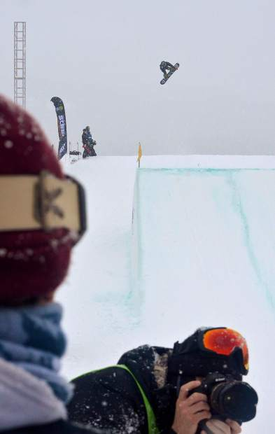 A snowboarder takes off from the big-air jump as photographers line the run-in during the men's snowboard slopestyle jump finals at Dew Tour in Breckenridge on Friday, Dec. 9. Competition continues today with ski and snowboard jib finals.