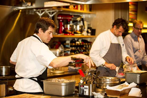 Bryan Nelson preps his work station for the Battle of the Chefs for Summit for Life against Chef Barclay Dodge, right, Friday night at the Aspen Cooking School.