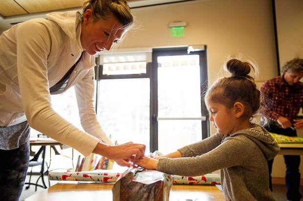 Jessica Chimerakis and her daughter, Cora, wrap holiday baskets at Christ Church in Aspen on Friday .  The holiday baskets hold gifts and City Market gift cards and are given to about 250 different families within the community that are in need.  Volunteers are still needed through Tuesday, December 2.  For more information on how to get involved inquire at this website: http://www.holidaybasketsprogram.com/get-involved.