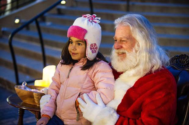 7-year-old Vanessa Varela takes a photo with Santa while waiting in line at Gorsuch for the AVSC sponsorship recipients.  Gorsuch gave away about 300 sets of ski equipment and D&E gave out about 100 sets of snowboarding equipment.