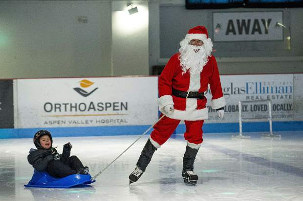 Santa pulls a little boy from Growing Years School in Basalt in a sled at the Lewis Ice Arena at the Aspen Rec Center on Wednesday morning. Santa's last day on the ice is today from 10:30-11:15a.m.