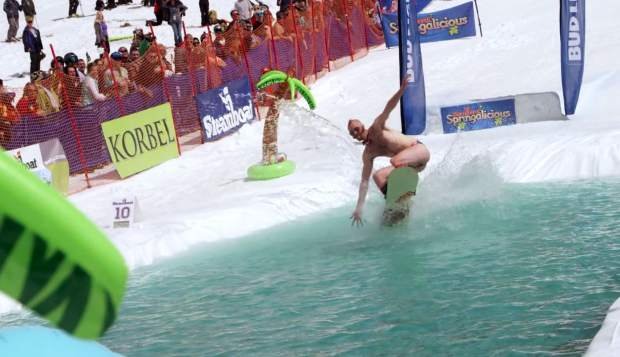 A snowboarder in a star-spangled man-thong gets wet at the Steamboat Springs pond skimming event for