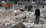 This frame grab from video provided on April. 19, 2014 by the Aleppo News Network, shows a man pointing to the aftermath of bombings of a cemetery in eastern Aleppo city, Syria. The old Aleppo cemetery filled up a year ago, the new one filled up this week, and now the dead are left in the besieged enclave's streets, buried in backyards and overwhelming the morgues. Dignity in death has been lost as the rebel-held enclave of eastern Aleppo that held out for four years collapses. (Aleppo News Network, via AP)