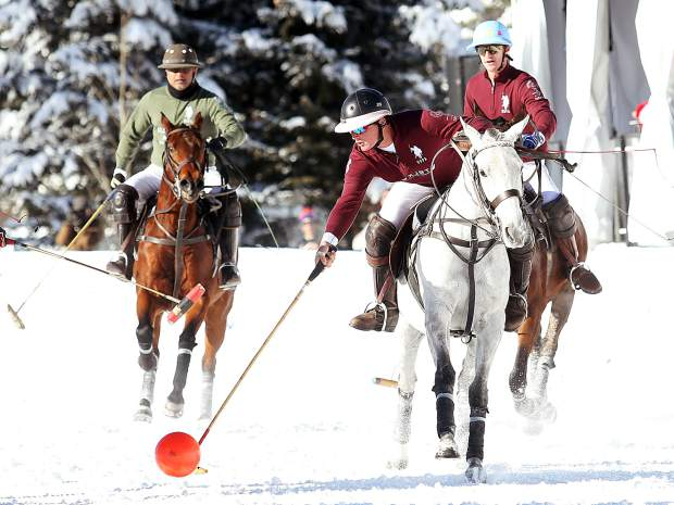 Flexjet's Jesse Bray leans over to strike the ball during Sunday's snow polo championship match. Bray was named the game MVP.