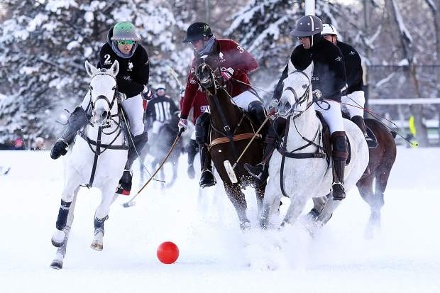 St. Regis, in black, plays team Audi in Sunday's snow polo consolation match in Aspen.