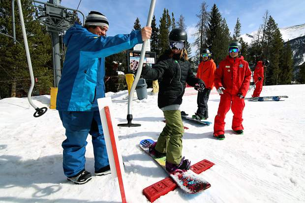 Students with a snowboard lesson load the Poma lift on the beginner terrain at Copper's West Village. The terrain-based teaching program at Copper takes students on custom-built rollers and berms to practice advanced techniques in a comfortable environment.