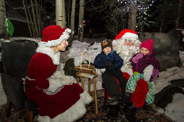 4-year-old Landon and 3-year-old Maddy Blasberg sit on Mr. and Mrs. Claus's laps at the Light Up the Night celebration at the Snowmass Chapel on Saturday night.