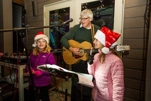 Josie Cole, 8, left and Lily Robins, 9, sing with Mack Bailey at the Light Up the Night celebration at the Snowmass Chapel on Saturday night.