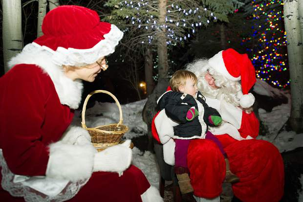 15-month-old Arabella Ramsey sits on Santa's lap at the Light Up the Night celebration at the Snowmass Chapel on Saturday night.