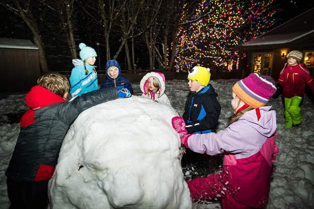 Children gather around a giant snowball at the Light Up the Night celebration at the Snowmass Chapel on Saturday night.