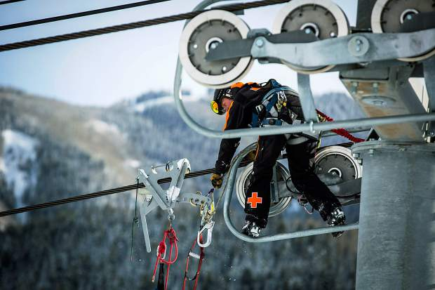A ski patroller prepares to descend down the lift line to reach the next chair.