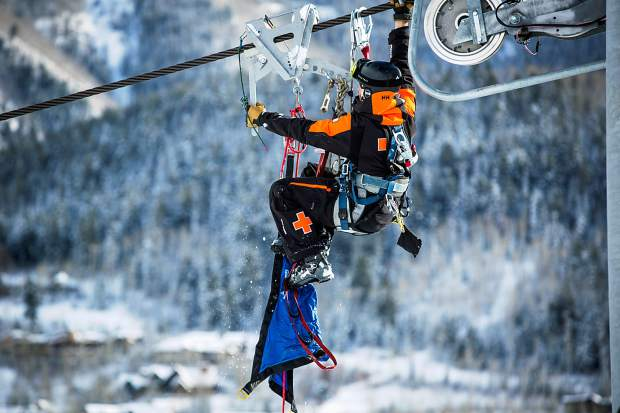 A ski patroller uses a safety device to descend to the next skier.