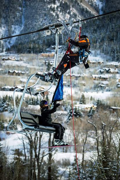 The skier attaches a harness to themselves and repels down to safety.