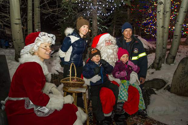 4-year-old Landon and 3-year-old Maddy Blasberg sit on Mr. and Mrs. Claus's laps with their parents Wes and Dawn behind them at the Light Up the Night celebration in Snowmass at the Snowmass Chapel on Saturday night.