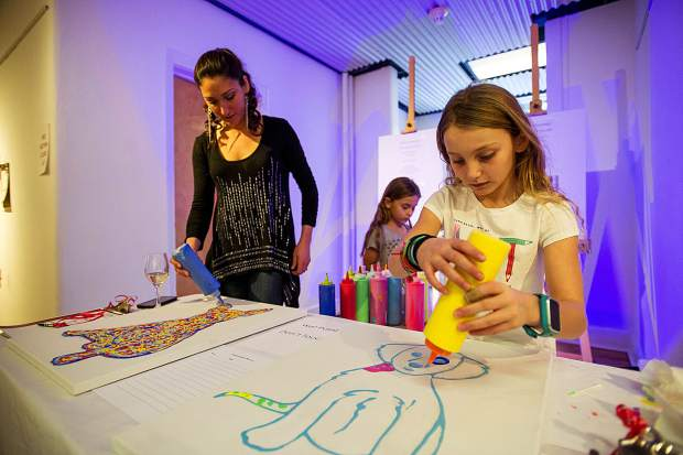 Local artist Rosalyn Pergande does live painting with her daughter Laila, 9, at the Valley Art Auction at the Red Brick Center for the Arts Tuesday night. All auction proceeds benefit the Red Brick's art education and outreach programs.