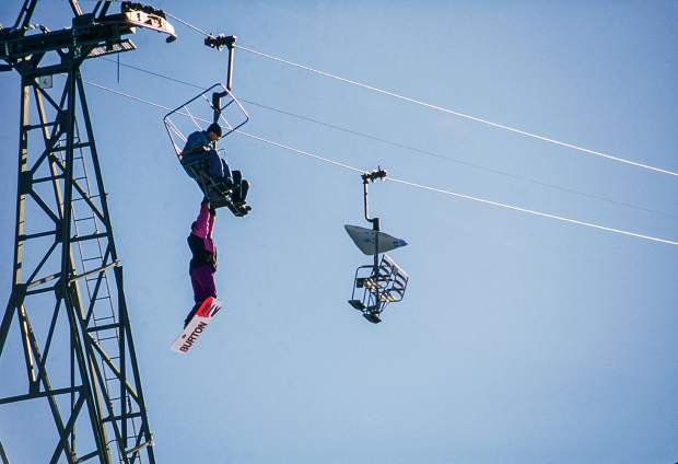 Craig Kelly (shot by Rod Walker) hanging from a chairlift in 1992. Kelly was one of the first snowboarders to take the sport deep into the backcountry and died in an avalanche in 2003.