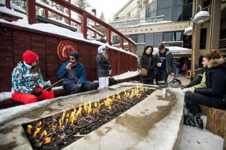 Skiers, snowboaders and shoppers keep warm and cozy by a fire on the Snowmass Mall.