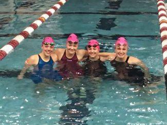 L.J. Fetzko, Davy Brown, Sarah DiPangrazio and Kennidy Quist take a break from warmdown after a meet. The quartet won two relays and 10 individual events at the Western Slope championships last weekend.