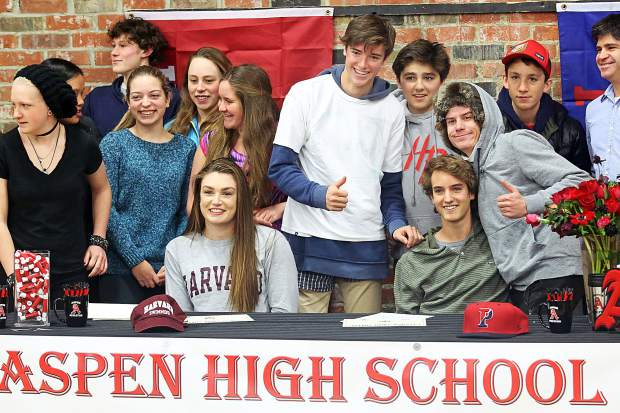Aspen High School seniors Kennidy Quist, seated left, and Matthew Lambert, seated right, are surrounded by teammates during Wednesday's National Signing Day ceremony in the Skier Dome. Quist will swim for Harvard while Lambert will play tennis at Penn.