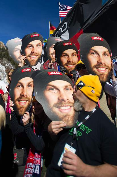 Fans hold up giant US skier heads of Travis Ganong before he raced at the men's Super-G competition on Thursday at Aspen Mountain.