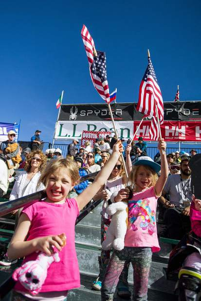 6-year-old local girls Linnea Bory, left, Devon Ryan, right, and Lyla Osborne fly their American flags high in the grandstands for the FIS men's and women's Super-G races on Thursday.