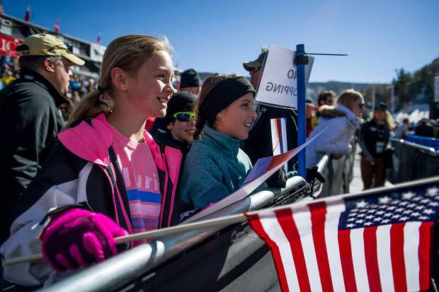 11-year-old Dallas residents Peyton Blalock, left, and Gigi Enrico wave their flags in anticipation of Lindsey Vonn coming over to sign their posters at the women's Super-G competition on Thursday.