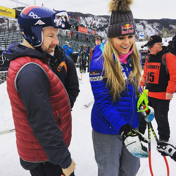 Retired ski racer A.J. Kitt, left, chats with American ski racer Lindsey Vonn on Monday as she signed autographs for this three children.