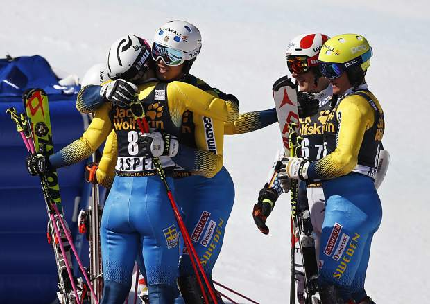 Sweden's Emelie Wikstroem, left, embraces Andre Myhrer as Sweden's Mattias Hargin, right, and Germany's Linus Strasser watch after a World Cup team event ski race Friday, March 17, 2017, in Aspen, Colo. Team Sweden finished first in the event. (AP Photo/Brennan Linsley)