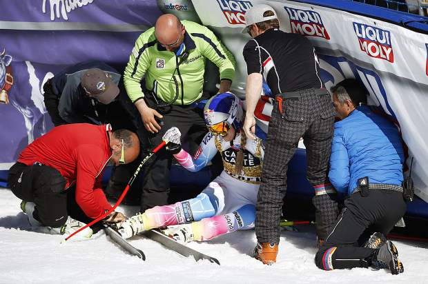 People help United States' Lindsey Vonn after she slid into a barrier following a run at the women's World Cup downhill ski race Wednesday in Aspen.