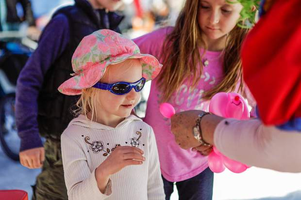 Addilyn Franze, 2, of Aspen has a balloon animal made for her at Wagner Park Family Fun Zone for the FIS World Cup Finals on Wednesday in Aspen.