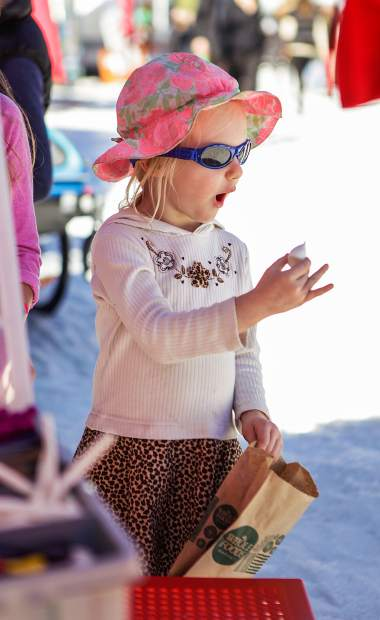 Addilyn Franze, 2, of Aspen is amazed at what she's eating at Wagner Park Family Fun Zone for the FIS World Cup Finals on Wednesday in Aspen.