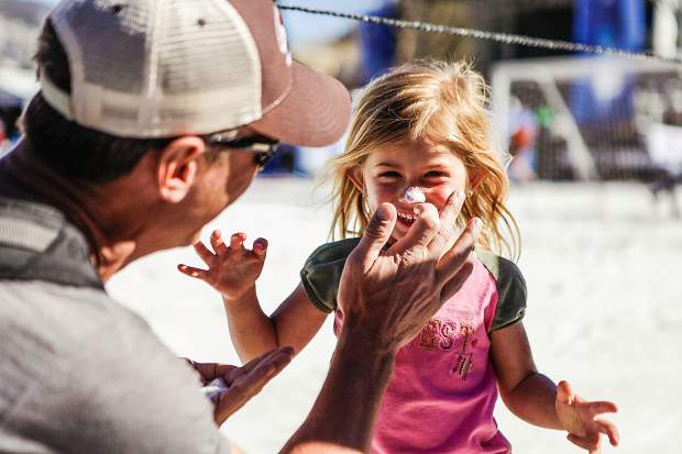 Mike Broggi of Fort Collins puts on sunscreen for Valentina, 3, at the Family Fun Zone in Wagner Park on Wednesday in Aspen.