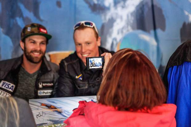 American skiers Travis Gonong, left, and Sam Morse take photos and sign autographs after the downhill at Wagner Park for the FIS World Cup Finals on Wednesday in Aspen. Races run through Sunday.